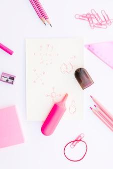 Канцелярские принадлежности вокруг химических формул и маркерной ручки