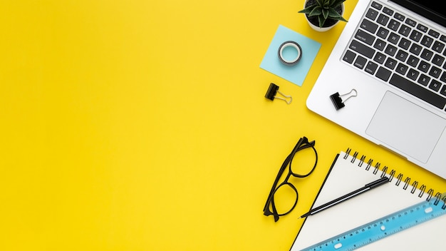 Stationery arrangement on yellow background with copy space