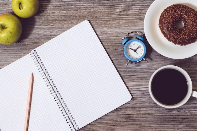 文房具の背景。開いたメモ帳、目覚まし時計、ドーナツが付いたプレート、ホットブラックコーヒーのカップ、木のテーブルの上のリンゴ