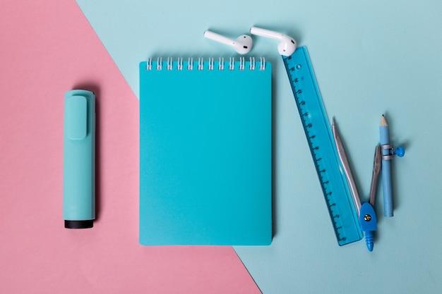 Канцелярские товары синего цвета блокнот, маркер, линейка и циркуль красиво разложены на розово-голубом фоне ...