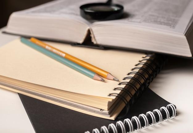文房具、本、ルーペ、鉛筆、ノートがクローズアップ。教育の概念