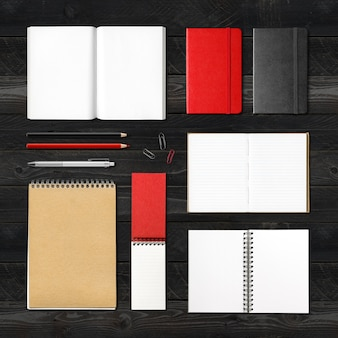 Stationery books and notebooks mockup template isolated on black wood background