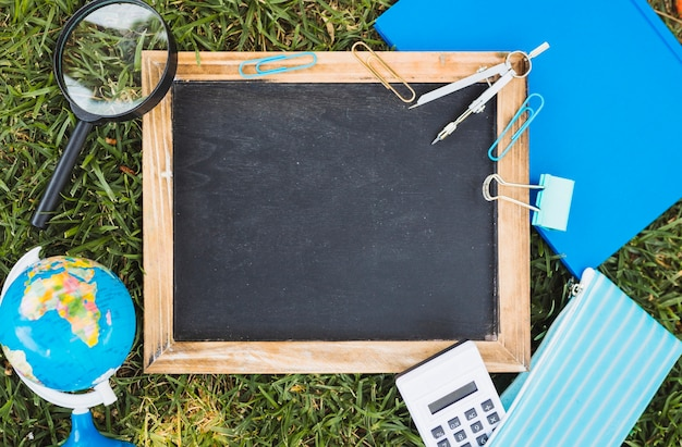Stationery and chalk board set on green lawn