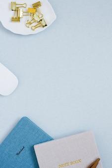 青い机の上にペンで文房具のクリップとメモ帳。ブロガーや学生のデスクトップ。コピースペース