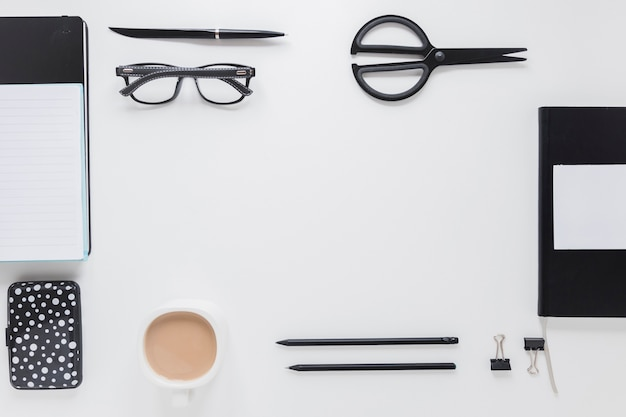 Stationery and coffee cup near glasses on white table