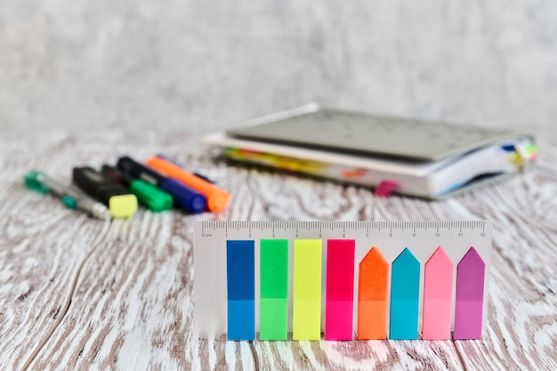 Канцелярские товары, цветные самоклеящиеся этикетки на переднем плане на деревянном столе, деловой натюрморт