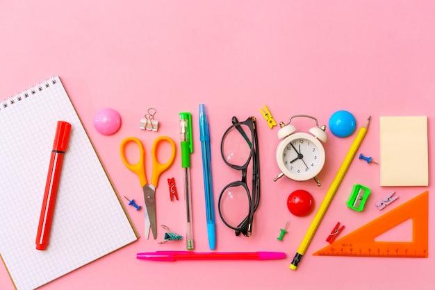 Канцелярские товары, красочные письменные принадлежности, ручки, карандаши, цветная розовая бумага, в качестве фона, обратно в школу ...