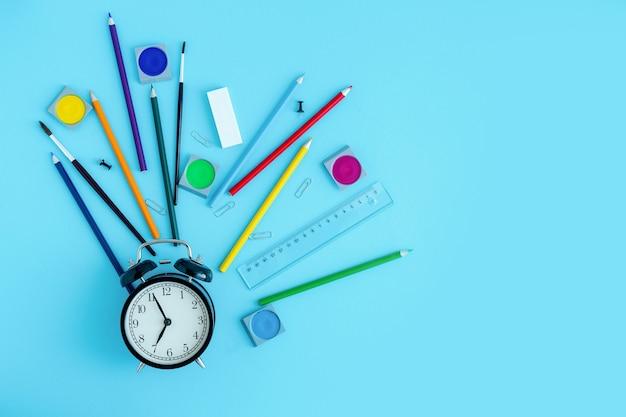 黒い目覚まし時計の周りの文房具、クレヨン、ブラシ、塗料