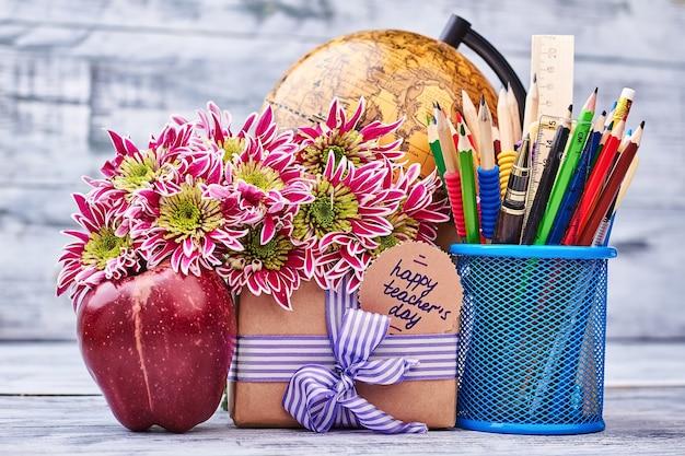 Канцелярские товары, цветы, глобус, подарок, яблоко. желаю вам счастливого дня учителя.