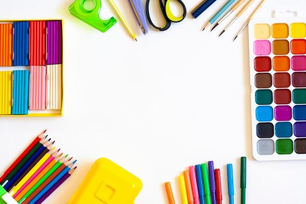 Канцелярские товары для школы и творческой работы на белом фоне, плоская планировка, копировальное пространство
