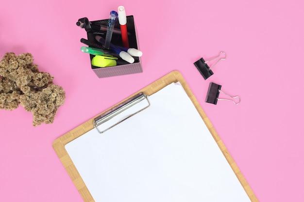 ピンクの背景に分離された研究のための文房具