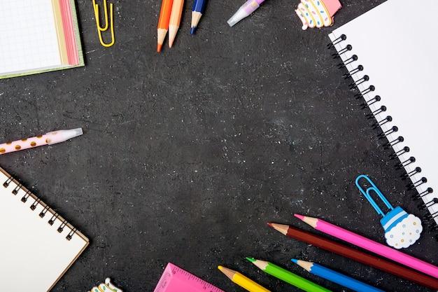 文房具は黒い背景にフレームを形成しました。コピースペースと学校のコンセプトに戻る