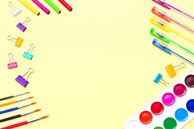 Рамка канцелярских принадлежностей на желтом фоне, плоский макет вида сверху цветных карандашей, ручек, кистей и акварелей, скрепок.