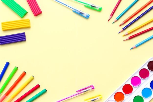 Рамка канцелярских принадлежностей на желтом фоне, плоский макет вида сверху цветных карандашей, ручек, кистей, пластилина и акварели, скрепок.