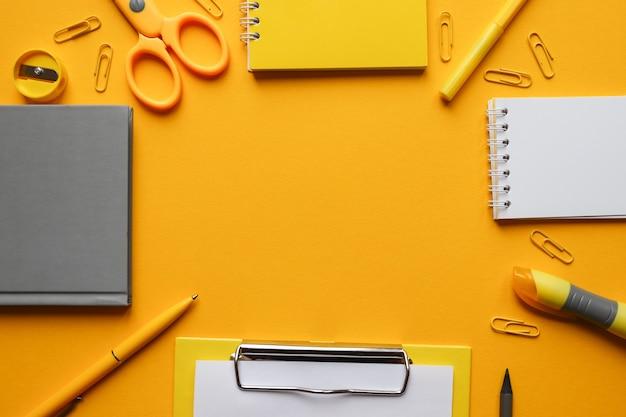 コピースペース付きのステーショナリーフレーム。明るいトレンディな黄色の背景に事務用品のある職場 Premium写真
