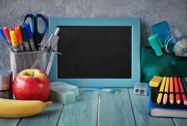 Stationery and fruits on a table in front of blackboard with text space