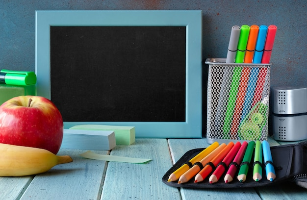 Stationery and fruits on a table in front of blank blackboard