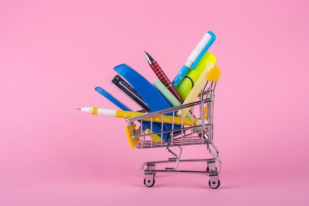 Канцелярские товары в тележке для покупок на розовом фоне