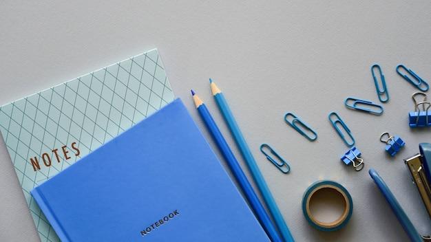 Канцелярские товары синего цвета и его оттенков на бумажном фоне. вид сверху. скопируйте пространство.