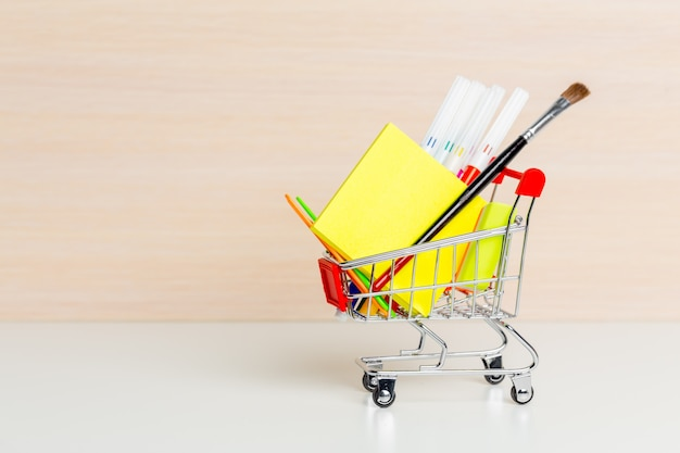 Stationery items in shopping trolley at left side