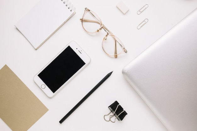Stationery and laptop near smartphone