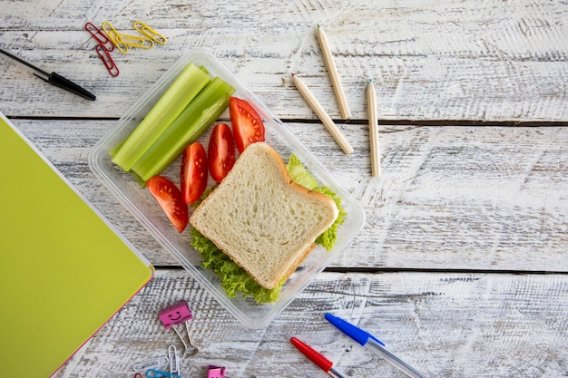 Stationery and lunchbox on table