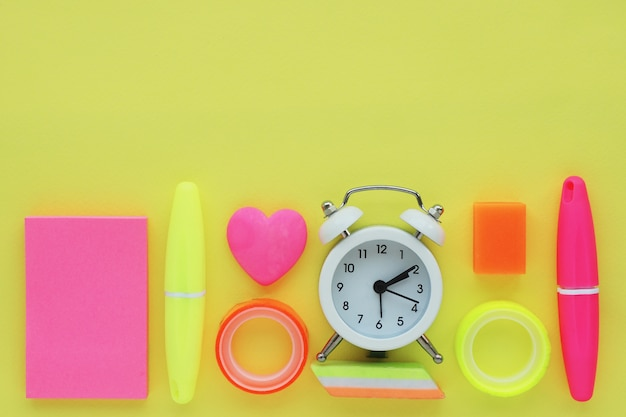 Stationery: markers, stickers, alarm clock, erasers of various shapes, colored tape. flat layout, top view on a yellow background. space for text.