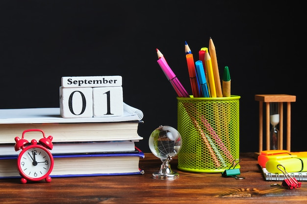 Канцелярские металлические стаканчики с карандашами рядом с книгами и сентябрьским календарем