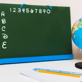 Stationery near chalkboard and globe