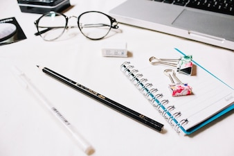 Stationery near glasses and laptop