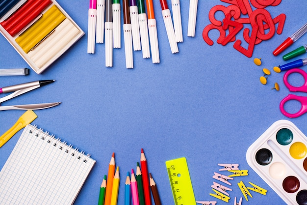 Stationery, objects for drawing and creativity are laid out in a frame on a blue
