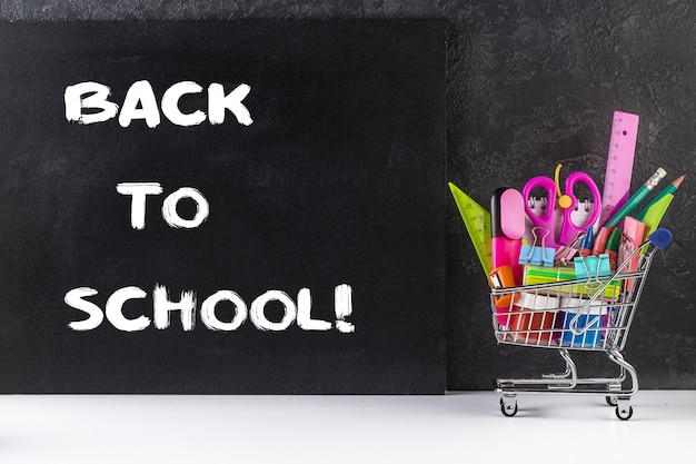 Stationery objects in mini supermarket cart on chalkboard background