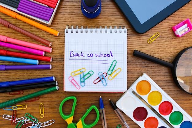 Канцелярские товары. школьные и офисные принадлежности. надпись: снова в школу