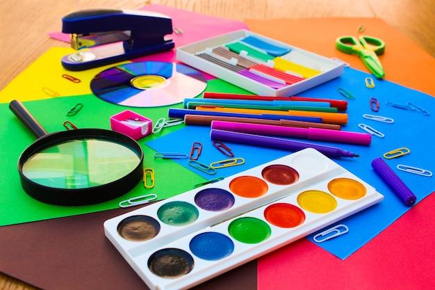 Канцелярские товары. школьные и офисные принадлежности на фоне цветной бумаги.