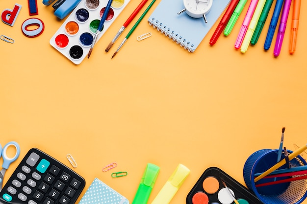 Stationery and office implements on orange table