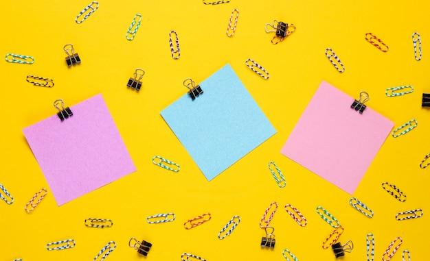 문구 사무용품. 컬러 메모 용지, 노란색 배경에 종이 클립.
