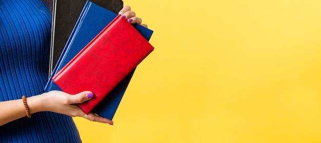 文房具、事務用品。現代のビジネスの必需品。女性の手でノートブックの品揃えのクローズアップ。モックアップカバー。