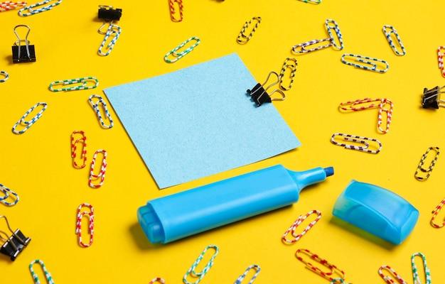 Канцелярские товары для офиса. скрепка, фломастер, памятка на желтом фоне