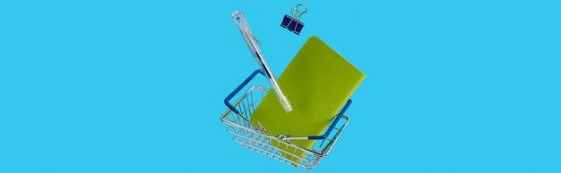 ショッピングカート付きの文房具事務用品は青い背景に浮揚します