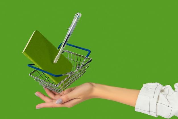 緑の背景に浮揚するショッピングカート付き文房具事務用品