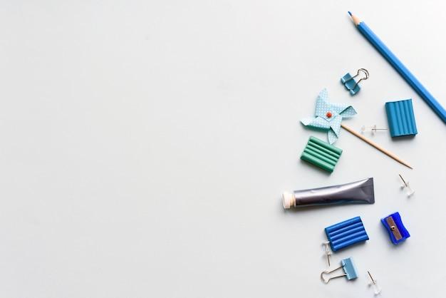 파란색 배경에 편지지입니다. 가위, 연필 및 플라스틱, 창의력을위한 아이템. 공간 복사