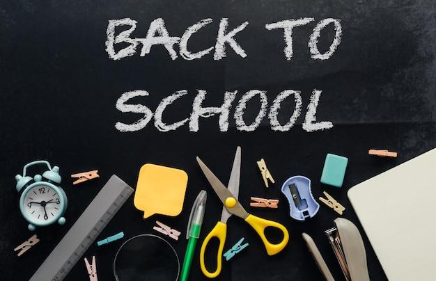 Канцелярские товары на потрепанном графитовом столе с остатками мела и надписью «снова в школу». шаблон для дизайна.