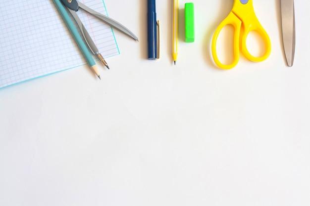 Канцелярские товары на белом фоне, ручки для ноутбуков, карандаши, компасы, ластик и ножницы, плоская планировка, пространство для копирования, вид сверху