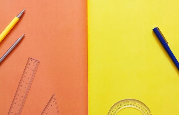 Канцелярские товары на оранжевой поверхности