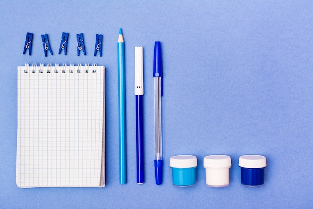 Stationery - open notepad, pencil, pen, felt-tip pen, gouache and clips blue background