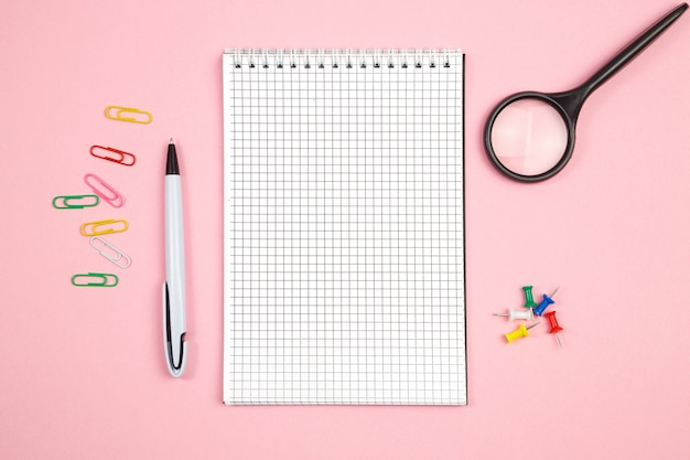 Stationery, paper notebook with pen and magnifier on pink isolated background. top view. flat lay. mockup