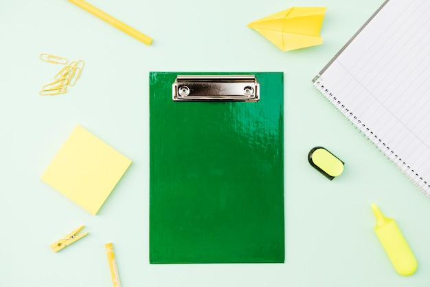 Stationery and paper plane around clipboard