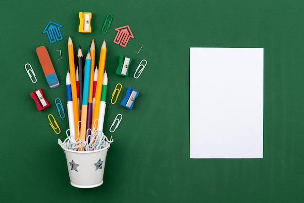 Stationery pencils paper clip pen eraser in a white bucket. still life on green school board background. copy space flat lay top view concept education