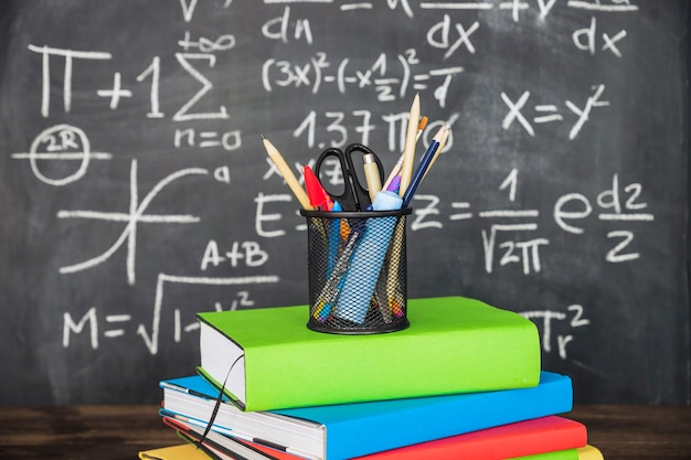 Stationery on pile of books near chalkboard