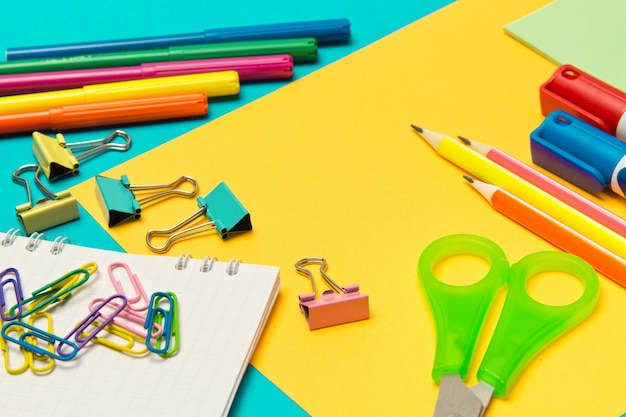 Канцелярские школьные и офисные принадлежности на цветном фоне